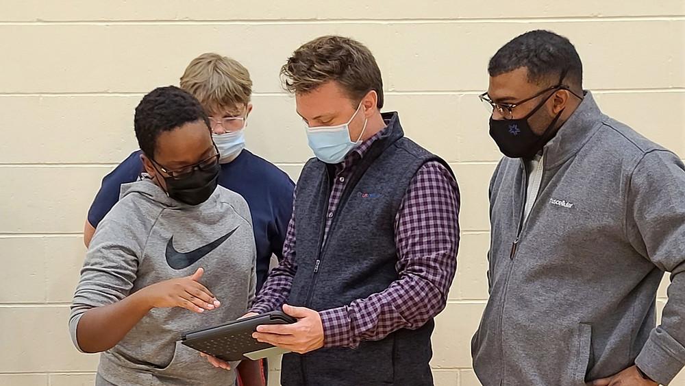 Students help UScellular associates program a robot from an iPad.