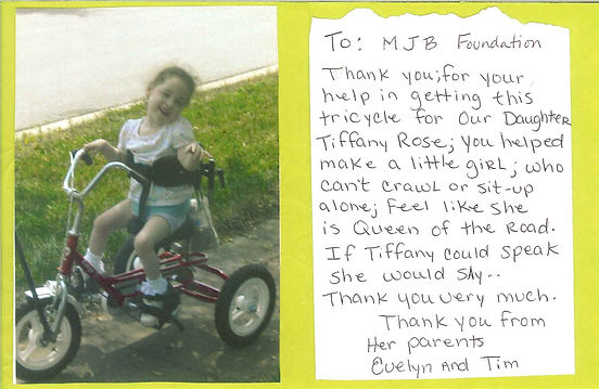 Tiffany on her specialized tricycle next to a thank you note from her parents, Evelyn ad Tim