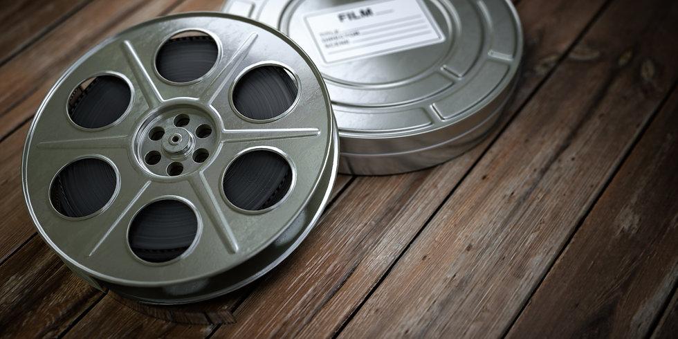 vintage-film-reel-with-filmstrip-on-wood