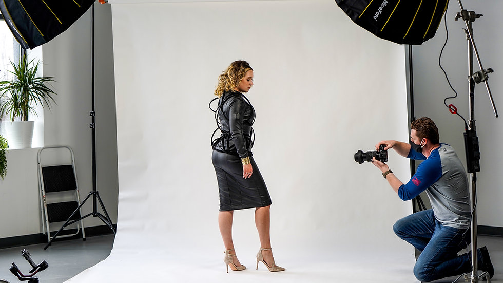 Model posing while videographer films