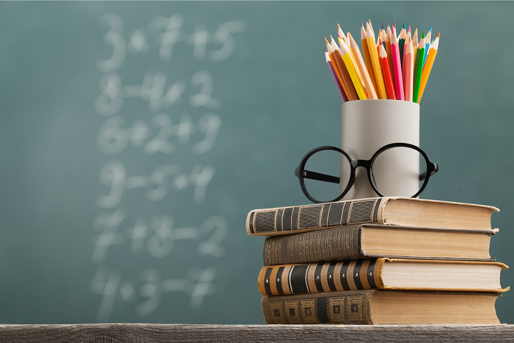 A stack of school books with a cup of colored pencils and glasses on top with a blackboard in the back values and curriculum
