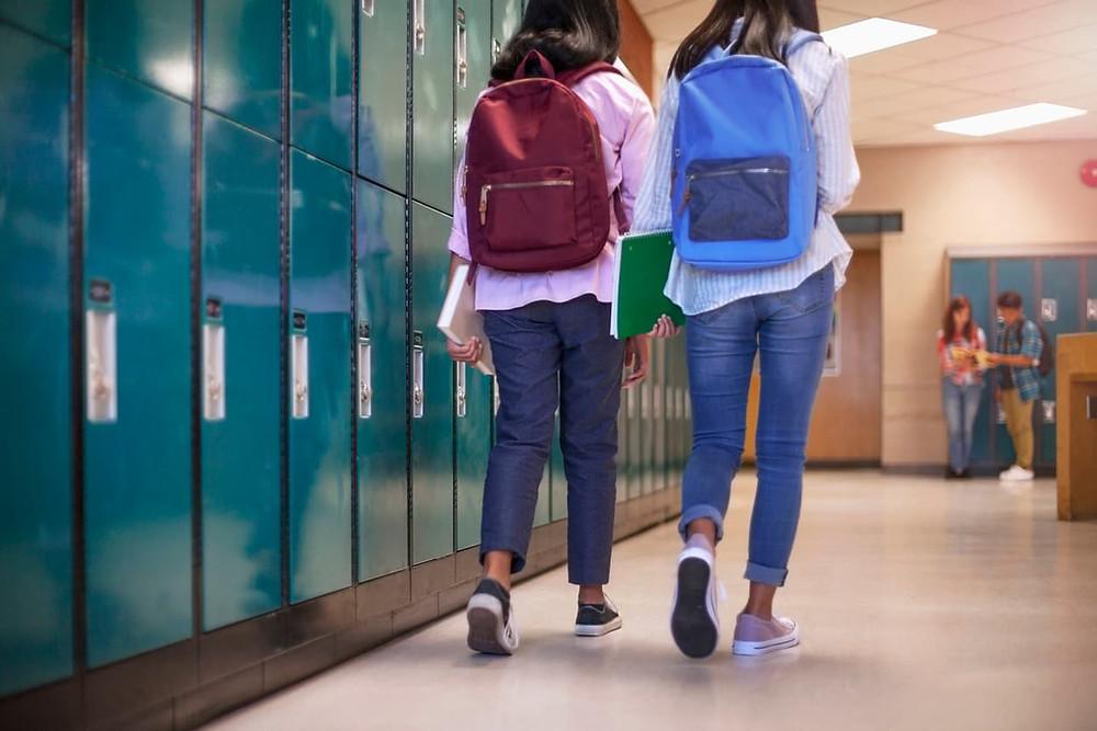 Two middle school girls walk down a hallway past lockers