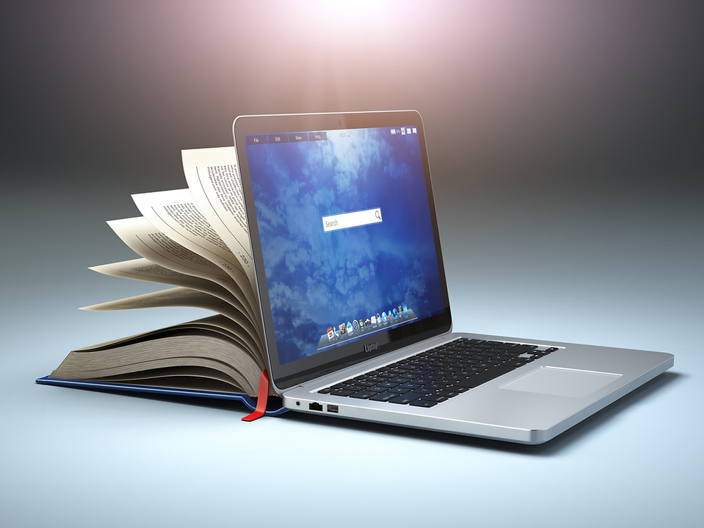 A Lamad Academy laptop leans against an open book for lifelong learning