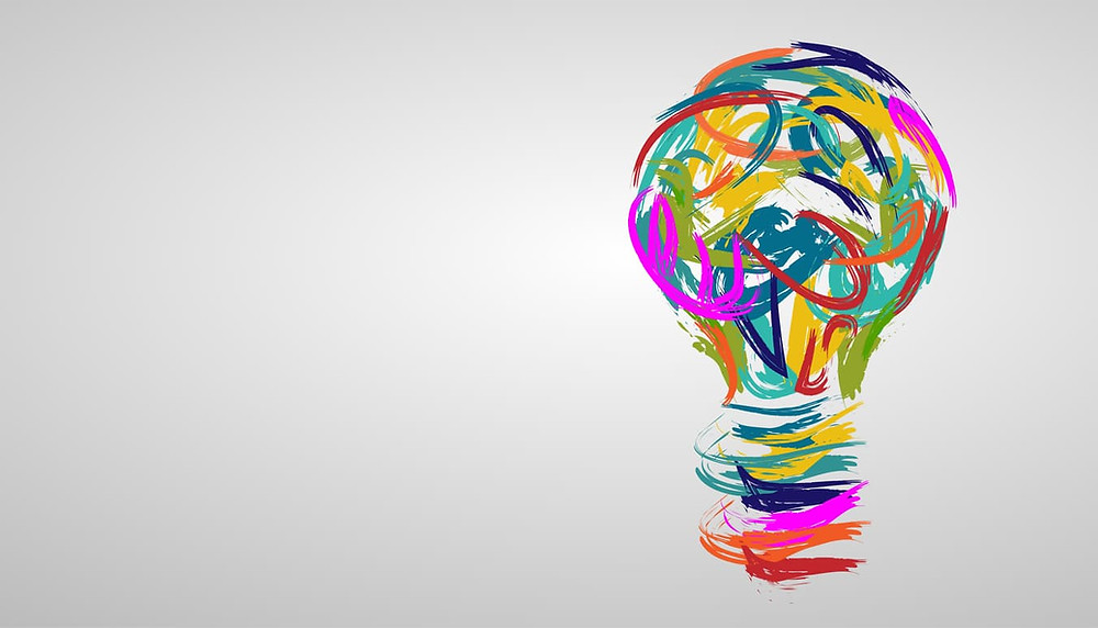 A lightbulb in various watercolors signifies STEAM