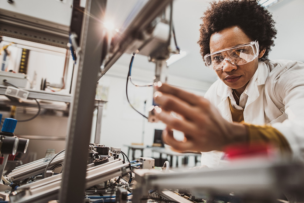 Female engineer works on an industrial machine in a laboratory as part of her STEM job