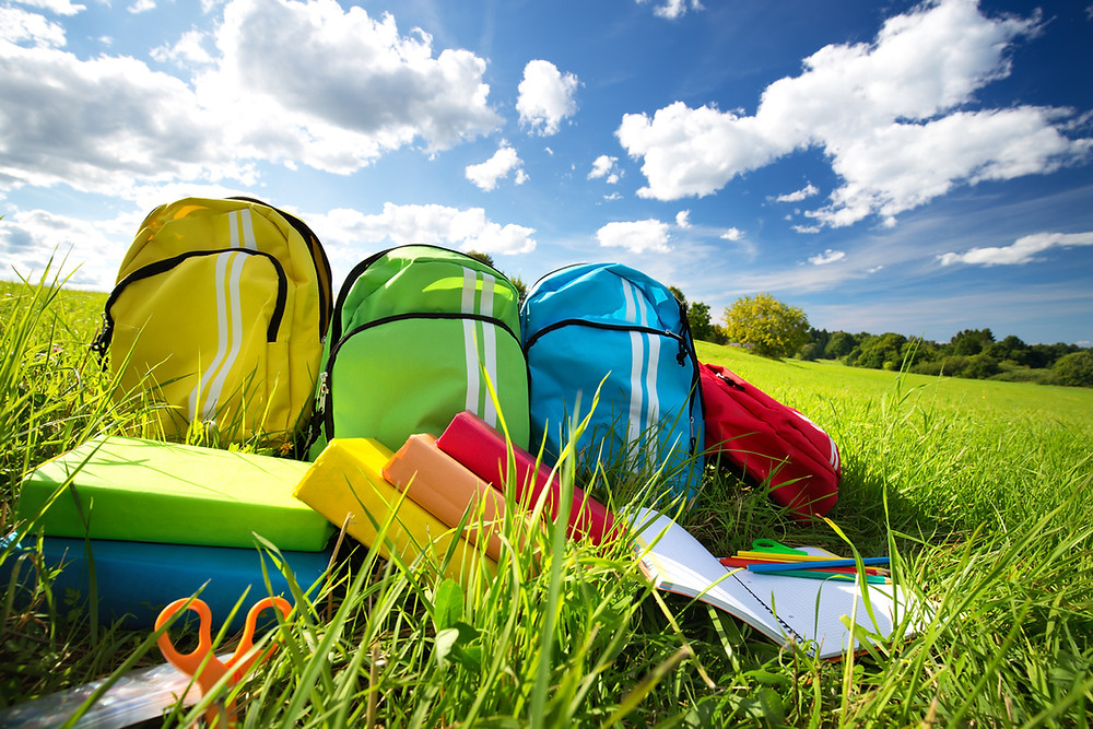 Colorful backpacks lined up on a grassy hill waiting for students to avoid the summer slide