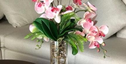 Orquídeas rosas en cilindro de cristal con ilusión acuática