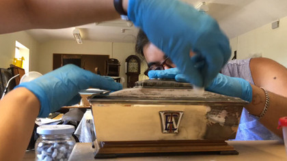 Tag team polishing a silver presentation chest at Brecknock Museum