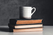 a-cup-of-coffee-on-stack-of-books-on-gre