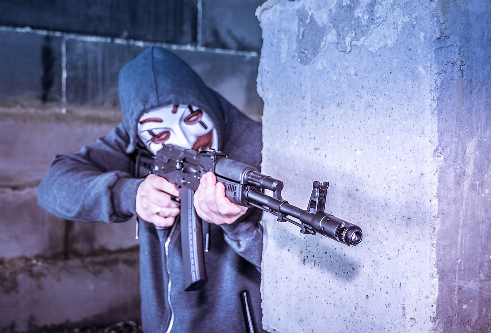 man in mask aiming to shoot from behind the wall