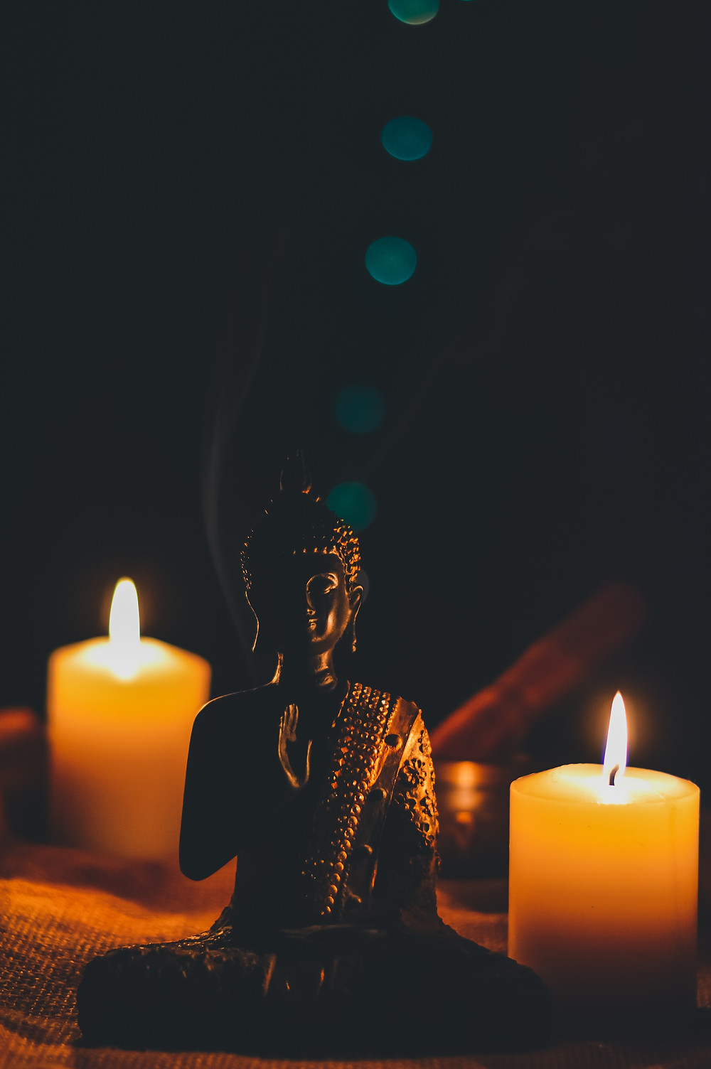 Buddha statue with burning candles.