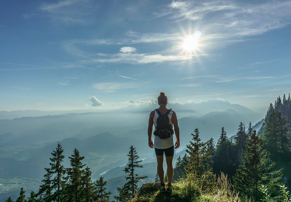 man standing on top of mountain and seeing view from there