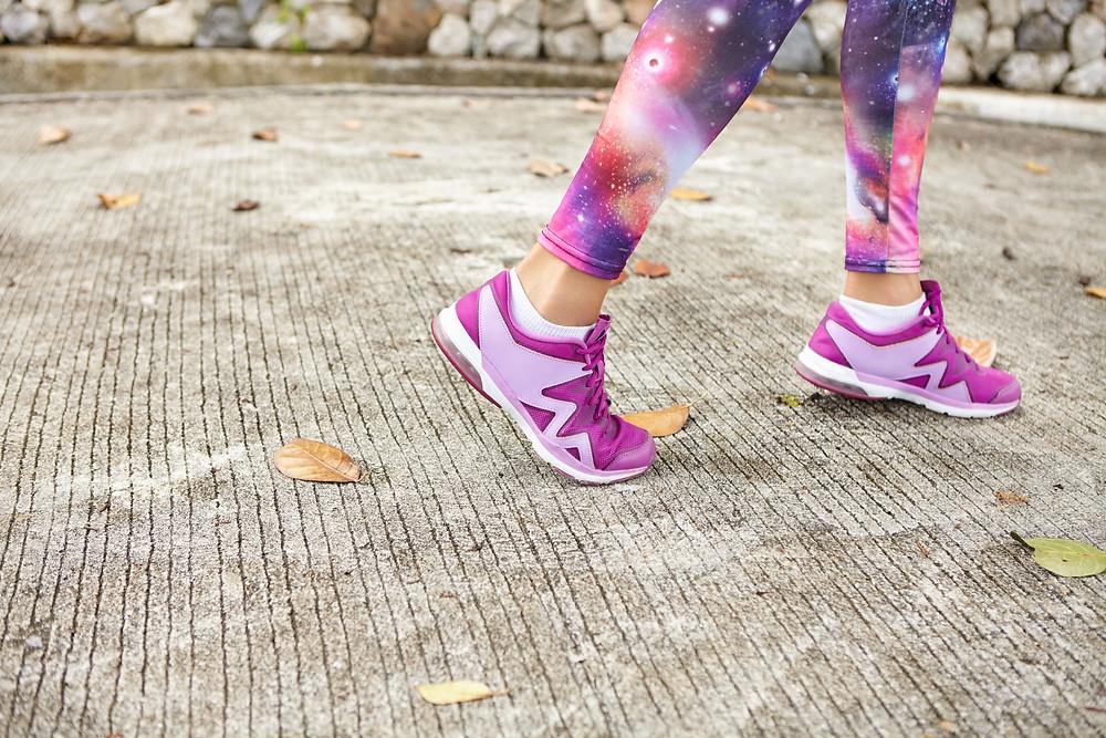 רגלי ספורטאית עם נעלי ספורט ורודות
