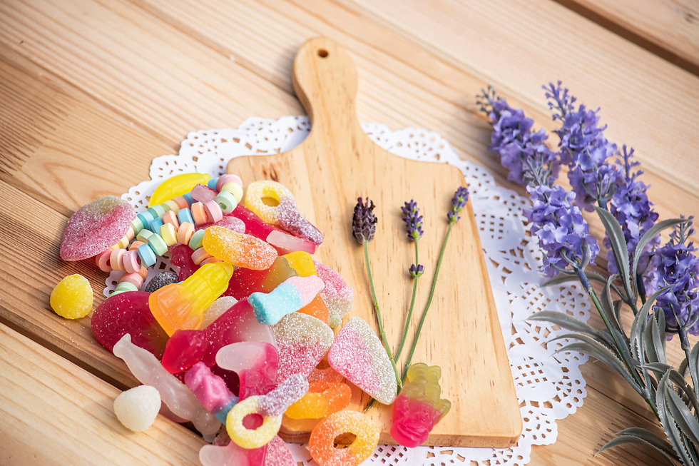 A selection of Jelly and Fizzy Pick N Mix displayed on a wooden board