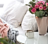 Cup of coffee and flowers on table near