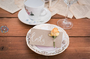 hand lettered wedding place cards decorated with a single yellow rose bud