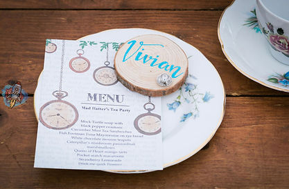 alice in wonderland themed menu card and small log slice hand lettered with wedding guest's name and embellished with a silver tea cup charm