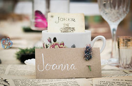 hand lettered wedding place cards decorated with a fresh wild flower
