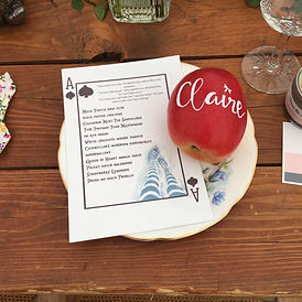 alice in wonderland themed menu card and wedding guest's name hand written on a red apple
