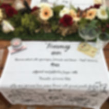 hand lettered / drawn Irish linen napkin used as a wedding favour and place setting - the wedding menu is written onto the napkin with fabric pen