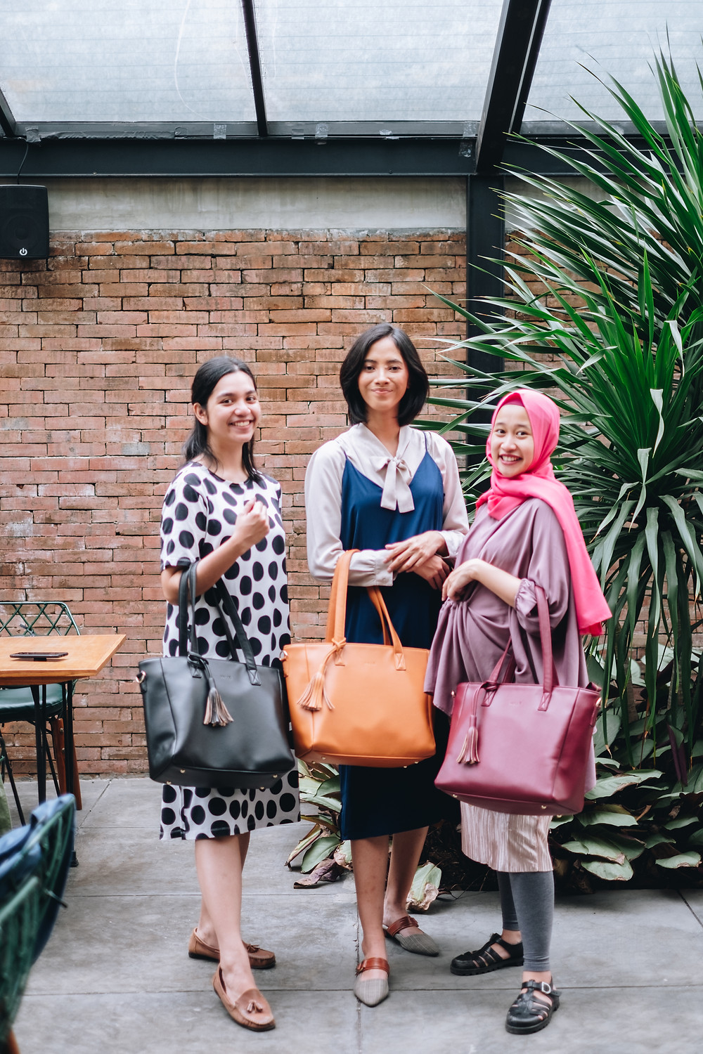 Intan, co-founder of Kalle (left), with a Kalle model (center) and Malika (right).