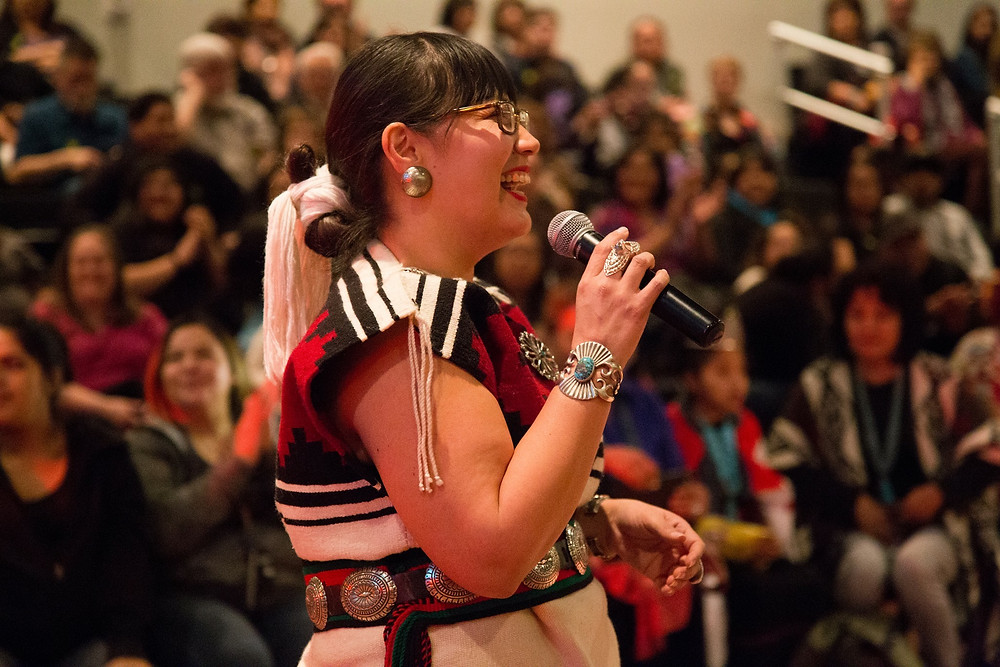 Jaclyn Roessel, founder of Grownup Navajo, speaking with a crowd. Photo by Roshan Spottsville. Interview with Toastee Mag.