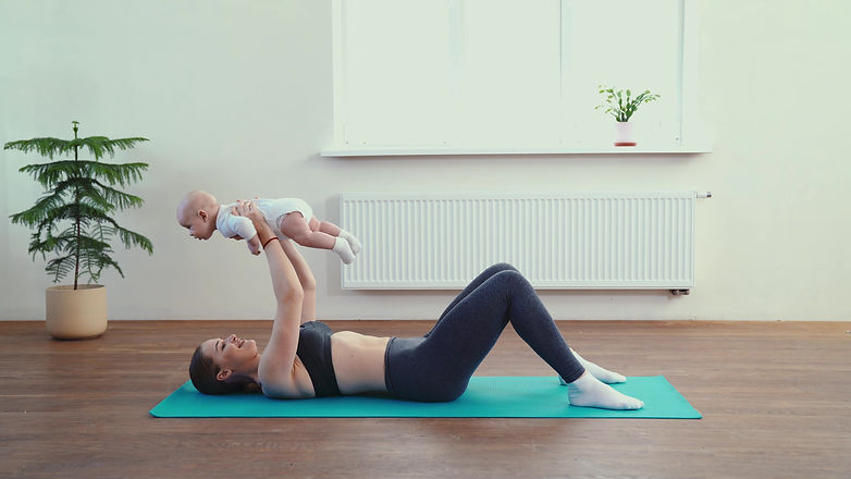 Young mother exercising with her baby bo