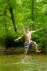 Boy jumping in a river in Delaware County New York