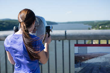Woman looking at the Hudson River with a telescope