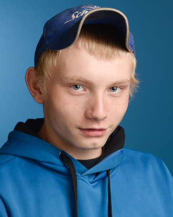 Headshot of a young man on a blue background in Andes New York