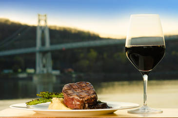 Cooked steak with mashed potatoes asparagus and wine with a bridge in the background