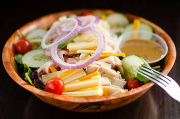 Salad in a wood bowel with dressing in Dehi New York