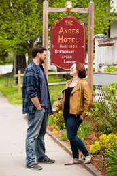 A man and a woman talking in front of the Andes Hotel in Andes New York