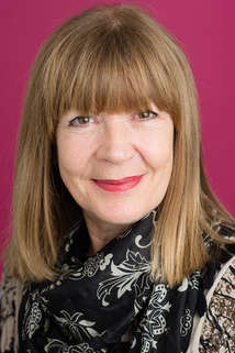 Headshot of a mature woman with a pink background
