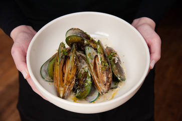Mussels in a bowel held by a wait person at The Peekamoose restaurant in Big Indian New York