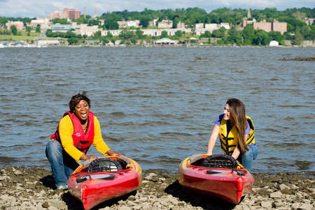 Two woman with canoes next to the Hudson river in upstate New York