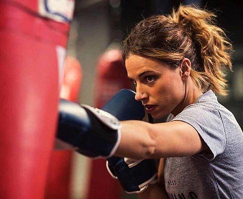 Littleton CO Fitness Kickboxing, The ROCK Martial Arts & Fitness, Fitness Kickboxing Girl punching a heavy bag