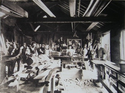 Inside the Workshop, with WJ supposedly carving the newel post for the Piccadilly Hotel.