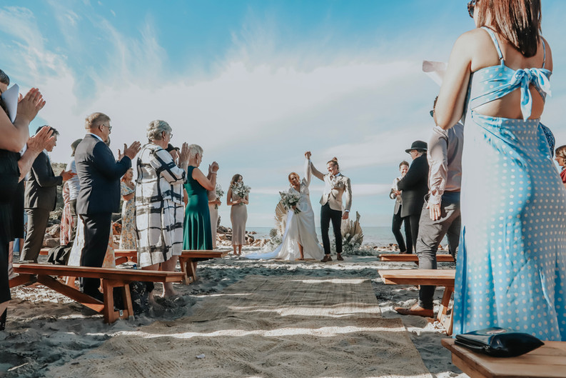 Wedding ceremony setup, wooden benches and rug aisle runner.