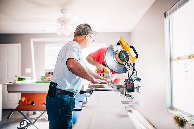 Tradespeople are using circular saws to cut wood in a home renovation.