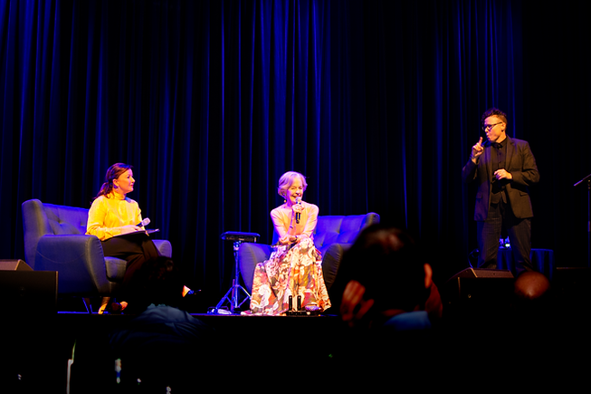 MC Kim Skubris is on the stage with Dame Quentin Bryce and an Auslan interpreter.