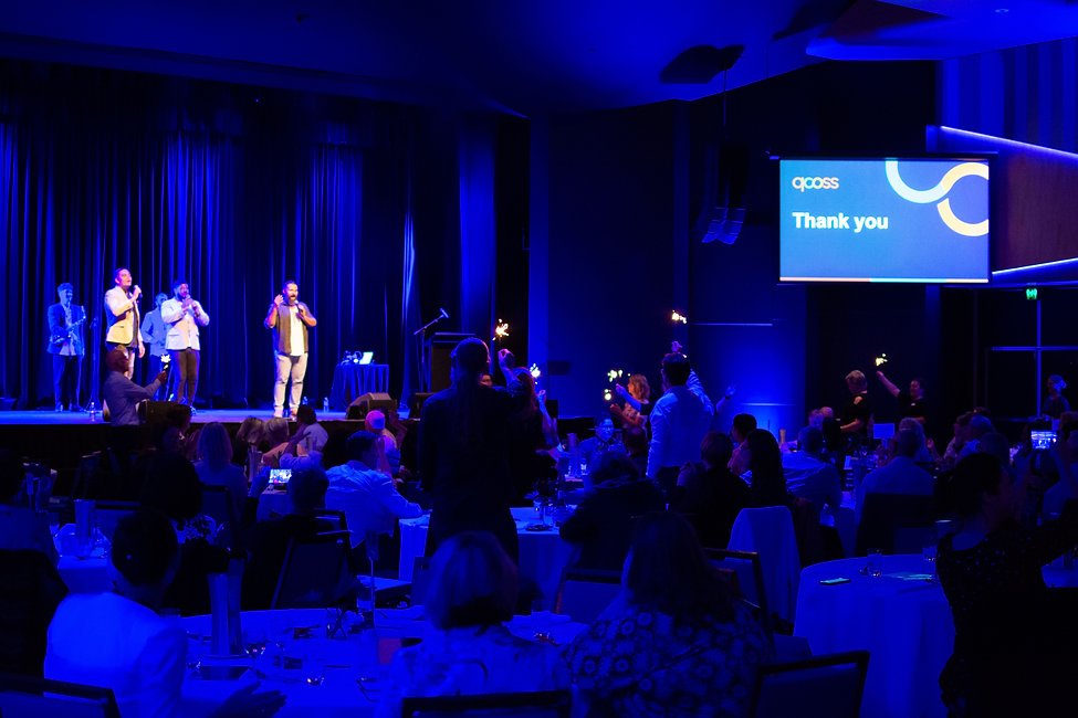 QCOSS staff are standing in a room of guests at the QCOSS 60th Anniversary Dinner event holding sparklers. Geed Up are peforming on stage.