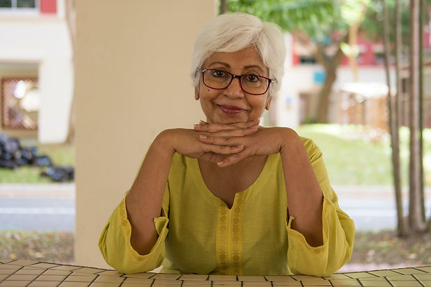 An older lady with grey hair is smiling with her head resting on her hands.
