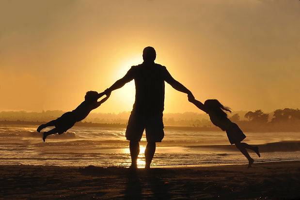 A man standing on a beach is swinging a child from each arm at sunset.