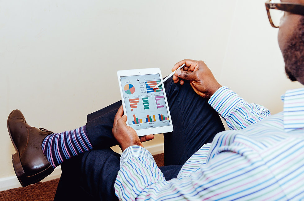 A businessman is assessing graphs and charts on a tablet device.