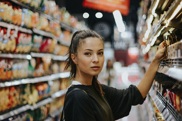 A young lady is shopping at a local grocery store. Her left hand is grabbing for an item off the shelf.