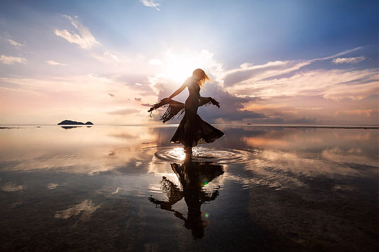 Elegant woman dancing on water. Sunset a