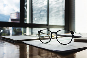 Glasses with documents on the table of b