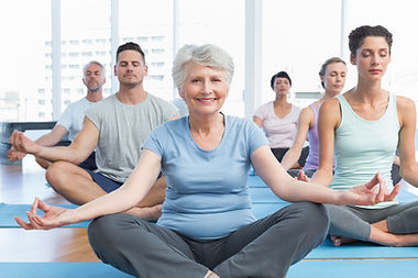 Older woman with group doing yoga