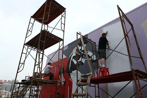 The Bogside Artists painting as part of the Dafen Mural Project 2010